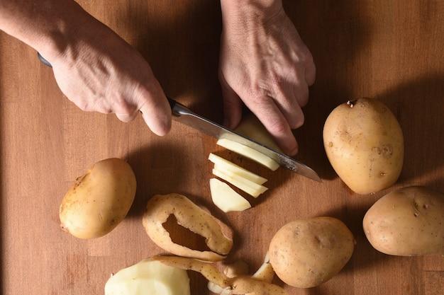 Hoge hoekmening van een kok die een aardappel in een bos snijdt