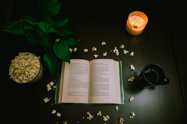 Hoge hoekmening van een open boek en popcorn op tafel met een aangestoken kaars en een kopje thee