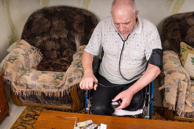 Hoge hoekmening van een oudere man met speciale behoeften die op zijn rolstoel zit en zijn bloeddruk controleert met behulp van een handmatig bp-apparaat in zijn huis.