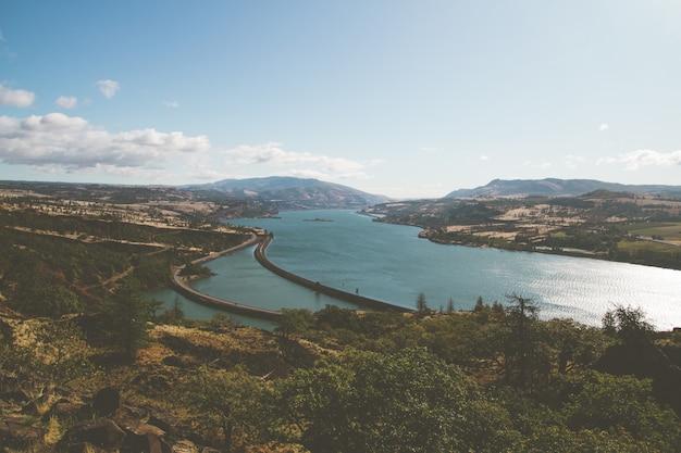 Hoge hoekmening van een rivier die door heuvels wordt omringd die in groen onder een blauwe hemel en zonlicht worden behandeld