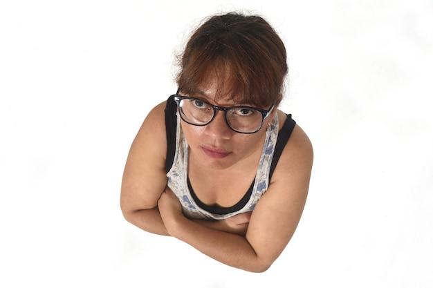 Hoge hoekmening van een serieuze vrouw gekruiste armen kijken naar camera op witte achtergrond