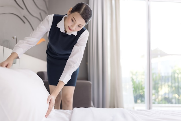Hoge hoekmening van een serveerster die het bed maakt, huishoudster die een hotelkamer schoonmaakt