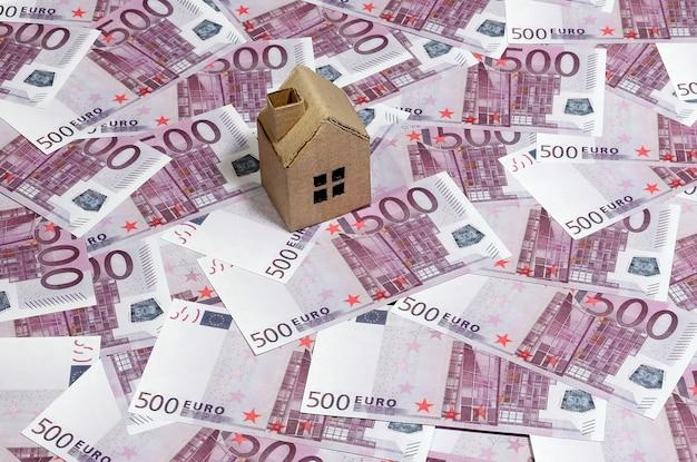 Hoge hoekmening van een speelgoedhuis van karton op 500 eurobiljetten