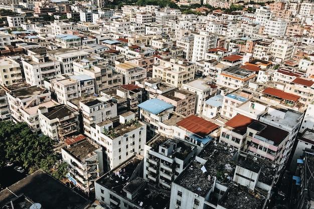 Hoge hoekmening van een stad bedekt met witte gebouwen en bomen onder het zonlicht