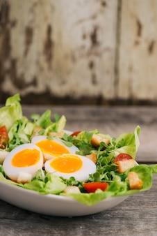 Hoge hoekmening van een voedzame groentesalade met gekookte eierschijfjes, geserveerd op een witte plaat op een houten tafel
