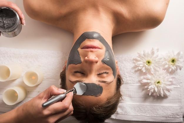 Hoge hoekmening van een vrouw die gezichtsmasker bij schoonheidssalon ontvangt