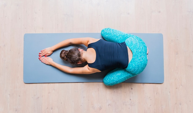 Hoge hoekmening van een vrouw die oefening op yogamat doet