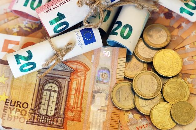 Hoge hoekmening van enkele opgerolde bankbiljetten en munten op meer bankbiljetten