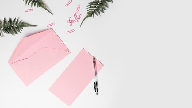 Hoge hoekmening van envelop; pen; kunstmatige varens en paperclips op witte achtergrond