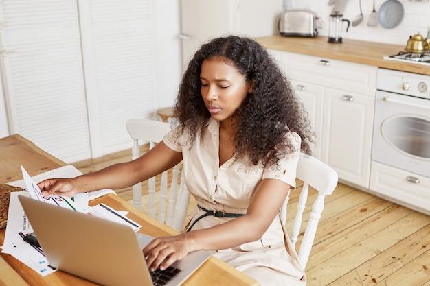 Hoge hoekmening van ernstige geconcentreerde jonge donkere vrouw met afro kapsel zitten aan de keukentafel in elegante jurk papieren en toetsen op generieke laptop houden, rekeningen online betalen