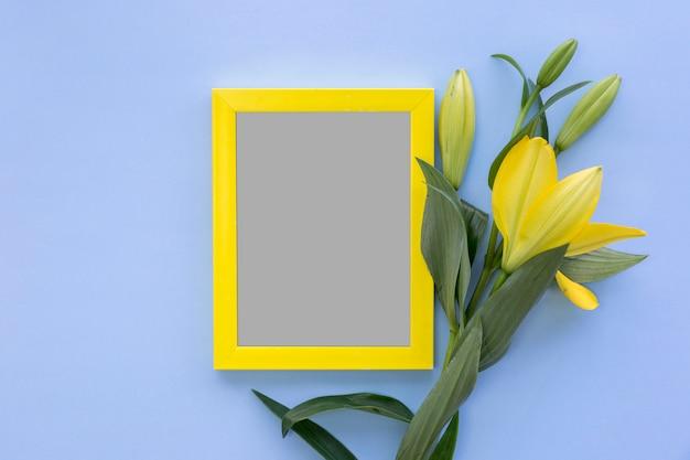 Hoge hoekmening van fotolijst en gele leliebloemen op blauwe gekleurde achtergrond