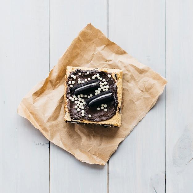 Hoge hoekmening van gebakje dat met koekjes op houten plank wordt verfraaid
