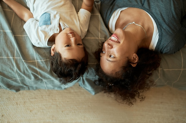 Hoge hoekmening van gelukkig mooi gemengd ras jonge moeder liggend op een deken op de vloer ondersteboven met haar schattige zoontje, hem sprookje vertellen