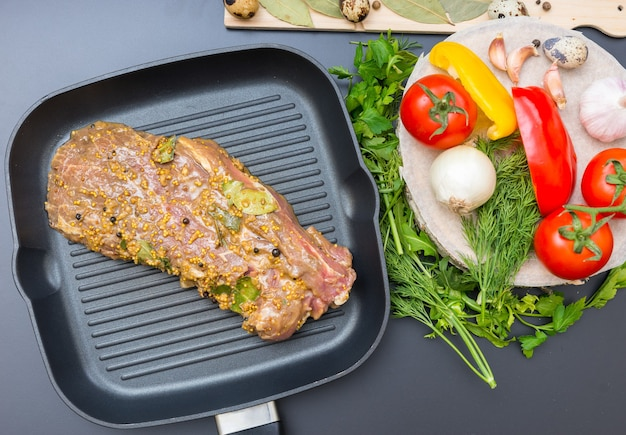Hoge hoekmening van gemarineerd vlees op een grillpan dichtbij groenten