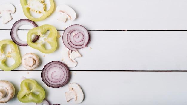 Hoge hoekmening van gesneden groene paprika; champignons en uien op houten achtergrond