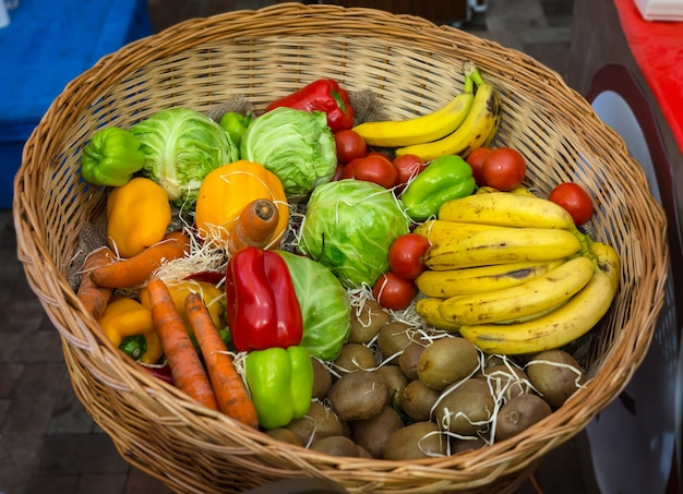 Hoge hoekmening van geweven mand gevuld met verse groenten en fruit - heldere en kleurrijke producten in rieten mand