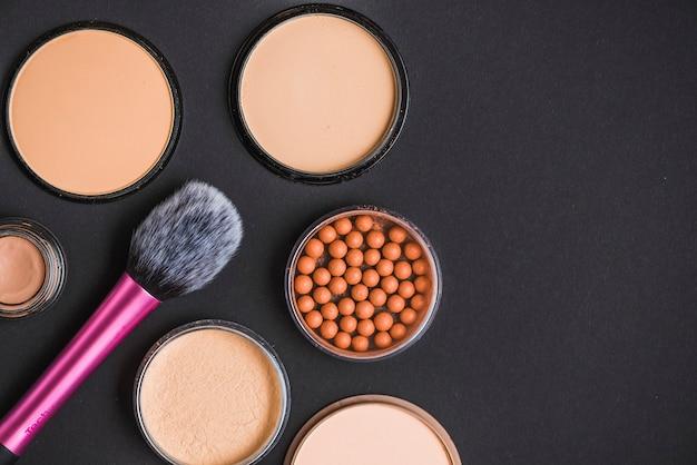 Hoge hoekmening van gezichtspoeder; bronzing parels en make-up borstel op zwarte achtergrond