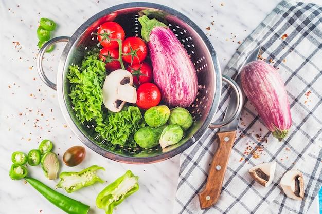 Hoge hoekmening van gezonde biologische groenten in vergiet over marmeren achtergrond