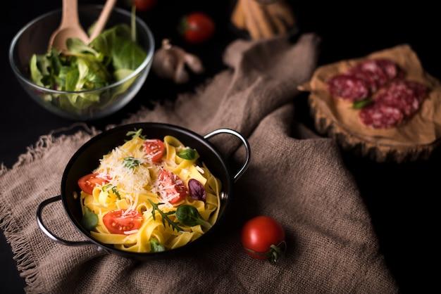 Hoge hoekmening van gezonde pasta in kookpot op jute textiel met cherry tomaat en salade