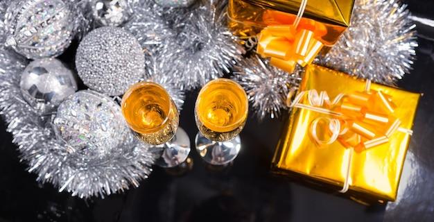 Hoge hoekmening van glazen champagne op donkere glanzende tafel met in goud verpakte geschenken, zilveren klatergoudslinger en kerstballen - feestelijk panoramisch stilleven