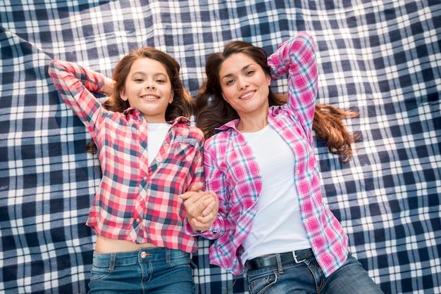 Hoge hoekmening van glimlachende moeder en dochter die op geruit patroondeken liggen