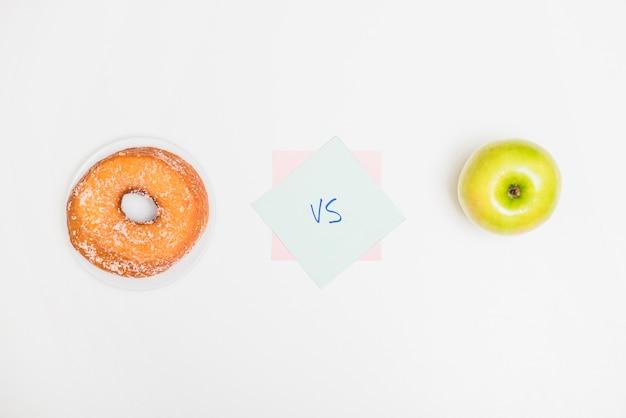Hoge hoekmening van groene appel tegenover doughnut op witte achtergrond