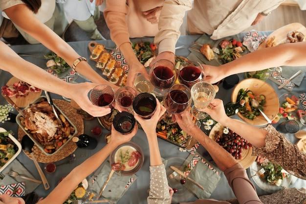 Hoge hoekmening van groep mensen die glazen houden en met rode wijn aan de lijst tijdens diner roosteren