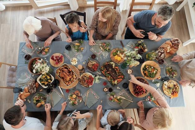 Hoge hoekmening van grote familie aan de tafel zitten en thuis samen eten