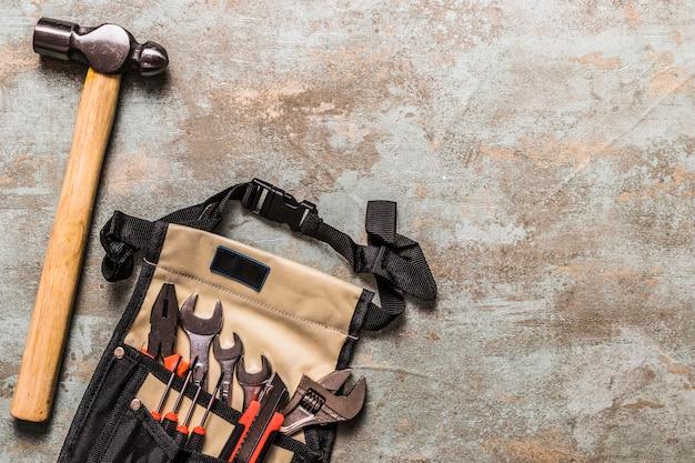 Hoge hoekmening van hamer dichtbij diverse hulpmiddelen in toolbag
