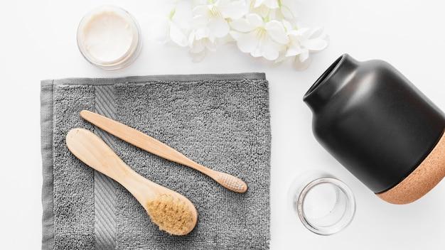 Hoge hoekmening van handdoek; borstel; hydraterende creme; bloemen en kruik op witte achtergrond