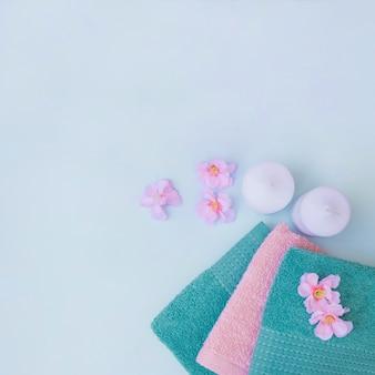 Hoge hoekmening van handdoeken; kaarsen en paarse bloemen op blauwe achtergrond