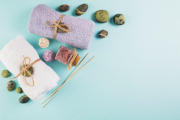 Hoge hoekmening van handdoeken; scrub fles en spa stenen op blauwe achtergrond