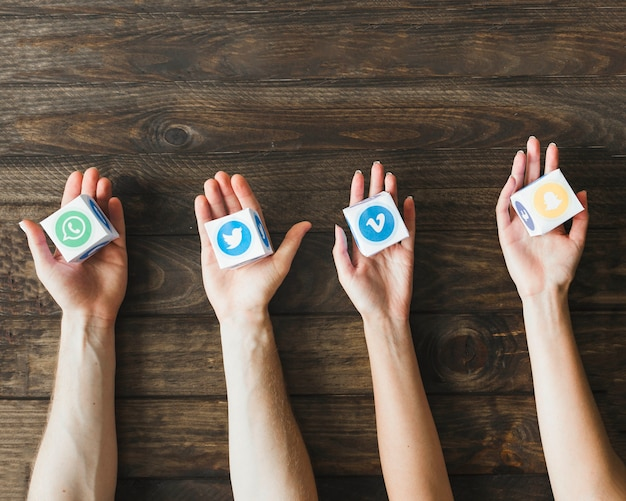 Hoge hoekmening van handen met vakken van levendige mobiele programmasymbolen
