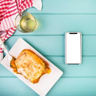 Hoge hoekmening van heerlijk eten en smartphone op tafel