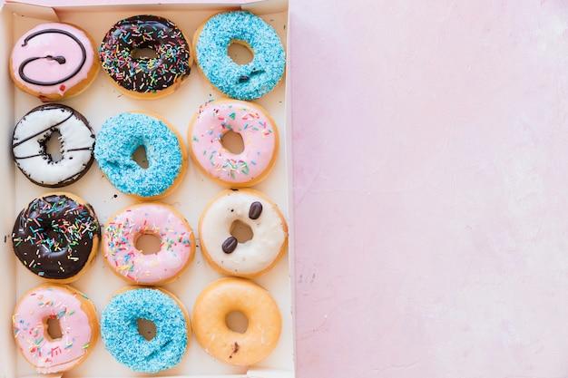 Hoge hoekmening van heerlijke donuts in vak op roze oppervlak