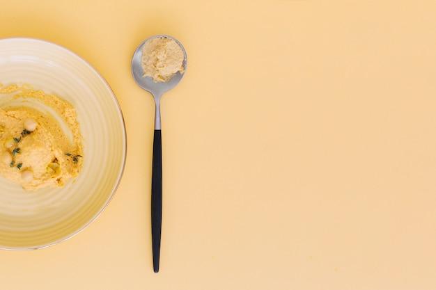 Hoge hoekmening van heerlijke hummus op gekleurde achtergrond