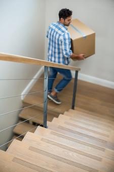 Hoge hoekmening van het kartondoos van de mensenholding terwijl het lopen op trap