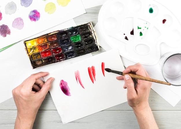 Hoge hoekmening van het menselijke hand schilderen op witte pagina met waterverf