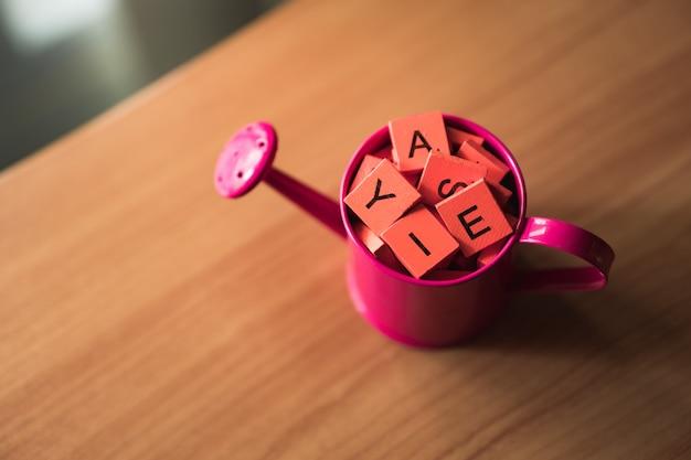 Hoge hoekmening van houten alfabet in gieter op bureau