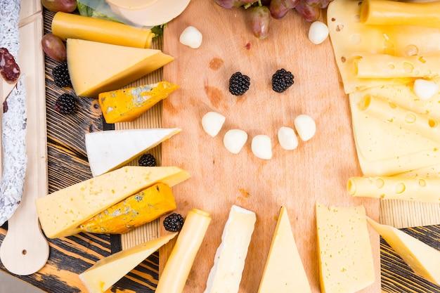 Hoge hoekmening van houten snijplank omringd door verschillende kazen en blij gezicht gemaakt van bocconcini en bramen