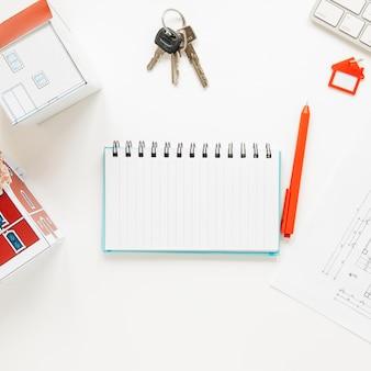 Hoge hoekmening van huismodel dichtbij spiraalvormige blocnote met sleutels en pen over witte achtergrond