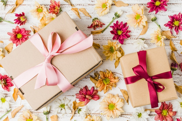 Hoge hoekmening van ingepakte giften en diverse bloemen over ruw bureau