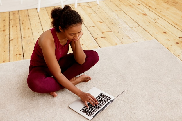 Hoge hoekmening van jonge afro-amerikaanse vrouw dragen beenkappen en top zitten met gekruiste benen op de mat voor open laptop, met behulp van wifi, op zoek naar tutorial, yoga thuis gaan beoefenen