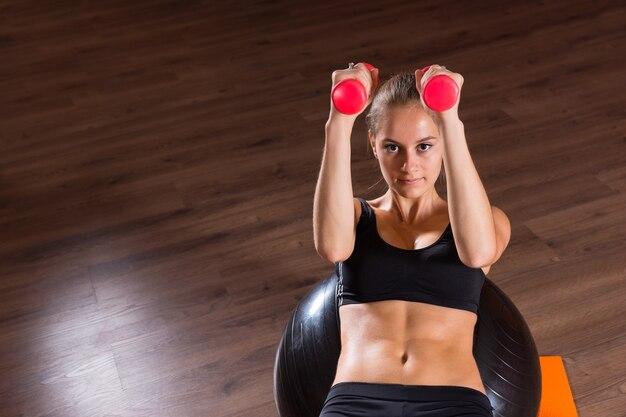 Hoge hoekmening van jonge blonde vrouw uitvoeren van abdominale crunches met handgewichten en balanceren op opblaasbare oefenbal in dansstudio met kopie ruimte