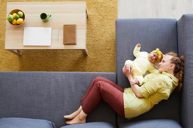 Hoge hoekmening van jonge moeder liggend op de bank en spelen met haar babymeisje thuis