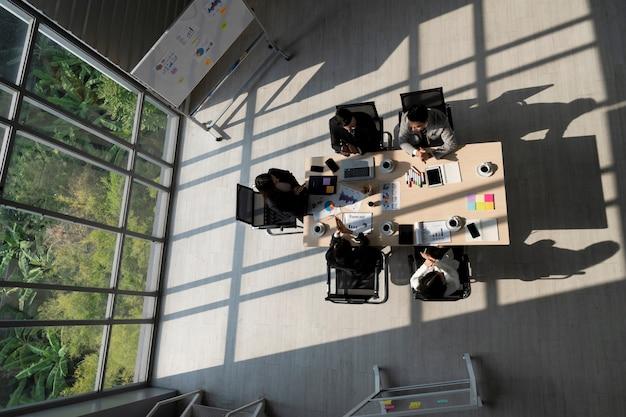 Hoge hoekmening van kantoorruimte met zakenmensen die aan tafel vergaderen en discussiëren met natuurlijk licht uit transparant raam met uitzicht op de groene tuin