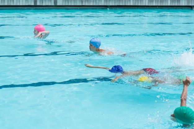 Hoge hoekmening van kinderen die in zwembad zwemmen