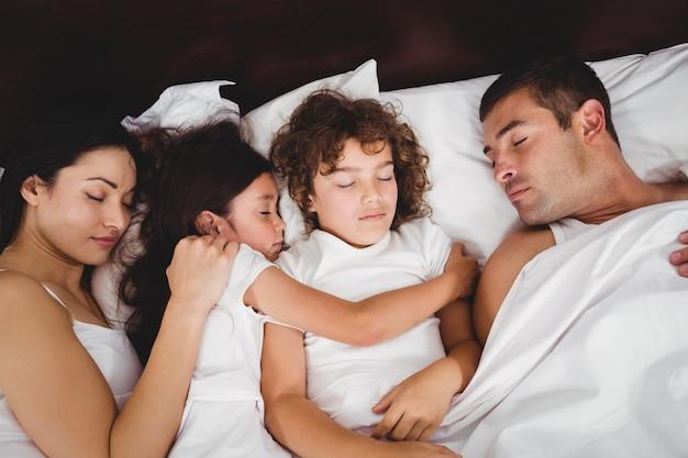 Hoge hoekmening van kinderen die met ouders op bed slapen