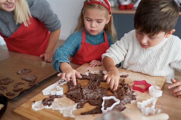 Hoge hoekmening van kinderen die peperkoekkoekjes uitsnijden