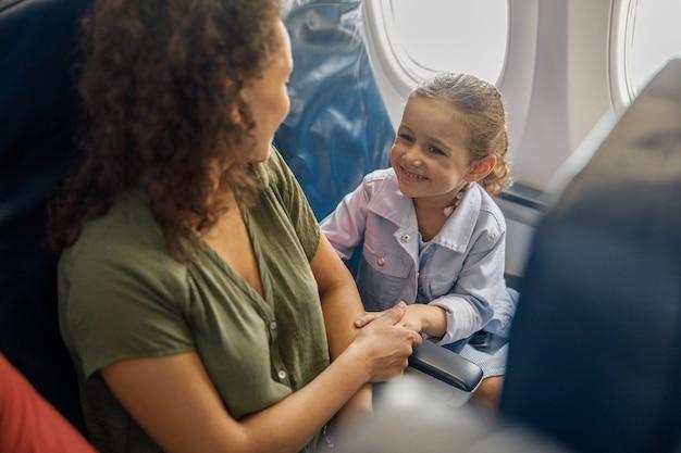 Hoge hoekmening van klein meisje zittend in het vliegtuig, glimlachend naar haar moeder terwijl ze samen reizen. familie, vakantieconcept